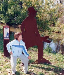A child strikes the pose of a nearby life-size steel silhouette of an I&M Canal pioneer along the I&M Canal.